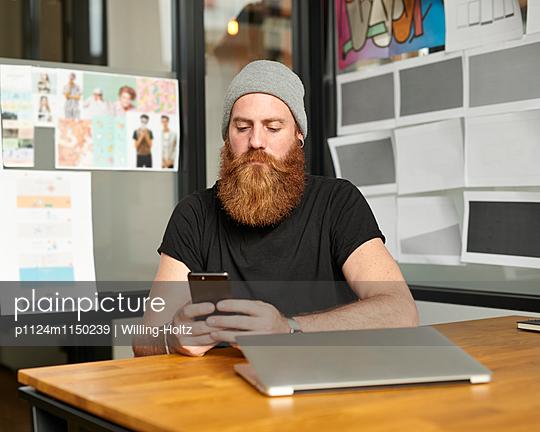 Designer mit Smartphone und Laptop am Schreibtisch - p1124m1150239 von Willing-Holtz
