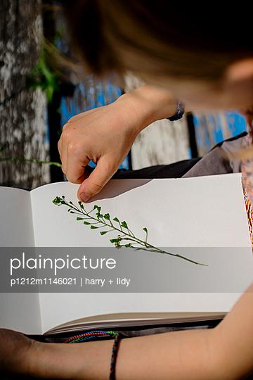 Mädchen bastelt in ihrem Heft - p1212m1146021 von harry + lidy