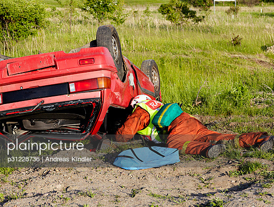 Firefighter lying near crashed car