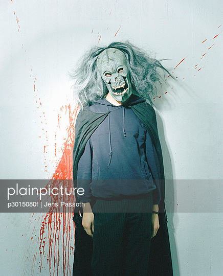 Person dressed up in spooky mask and wig in front of blood splattered wall