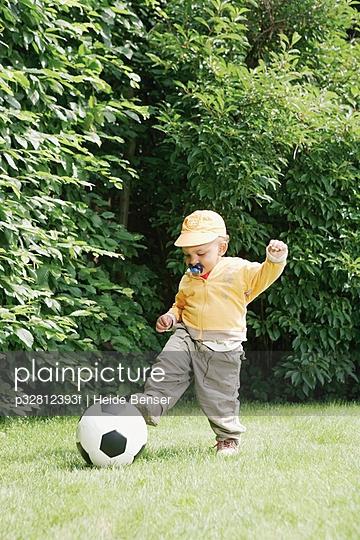 Toddler kicking soccer ball