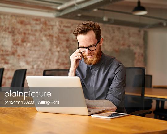 Junger Mann telefoniert am Arbeitsplatz - p1124m1150200 von Willing-Holtz