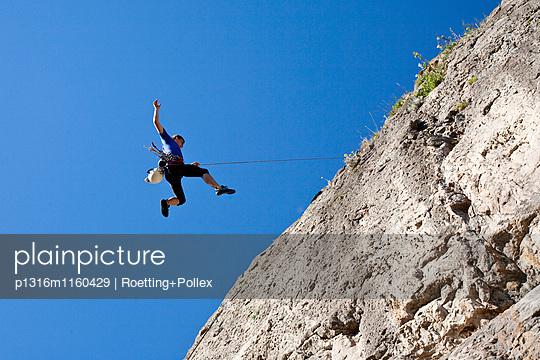 Kletterer beim Abseilen von einer Felswand unter blauem Himmel, Jerzu, Sardinien, Italien, Europa - p1316m1160429 von Roetting+Pollex