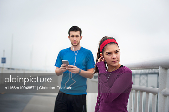 Confident female athlete wearing earphones while standing with friend on Bay Bridge