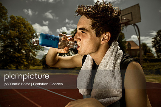 Portrait of young basketball player drinking water out of bottle