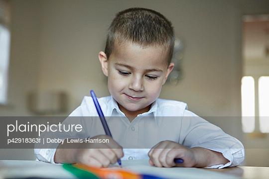 Schoolboy writing at desk