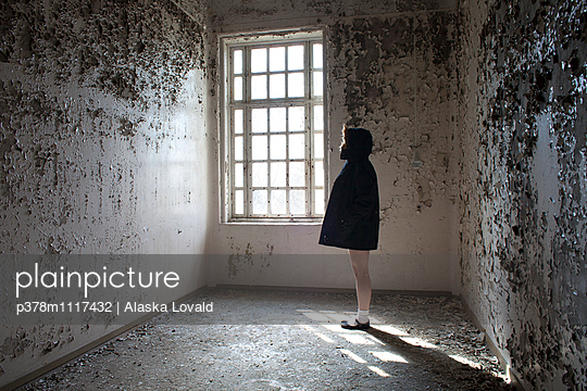 Young woman wearing a coat standing in a derelict empty room lit by window. Lier, Norway