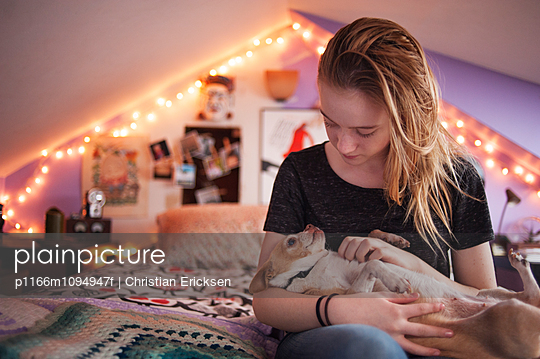 Girl playing with Chihuahua while sitting on bed at home