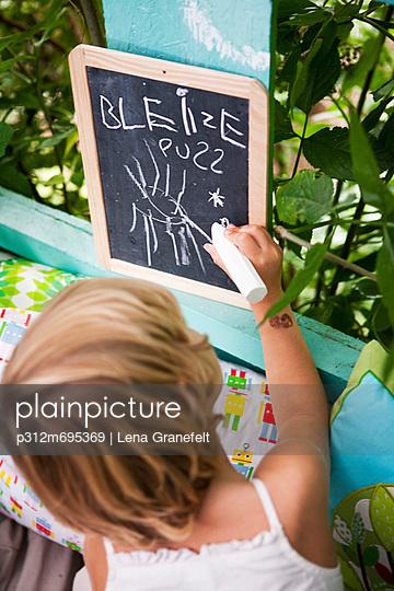 Girl writing with chalk on slate
