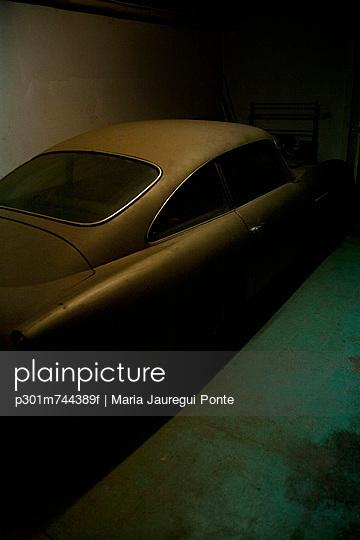A vintage car parked in a dark garage