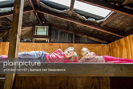 Zwei Mädchen auf dem Bett einer Hütte, Tramping Fjordland, Lake Manapouri, Südinsel, Neuseeland - p1316m1161157 von Bernard van Dierendonck