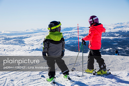 Siblings in ski-wear standing on snowcapped mountain against clear sky