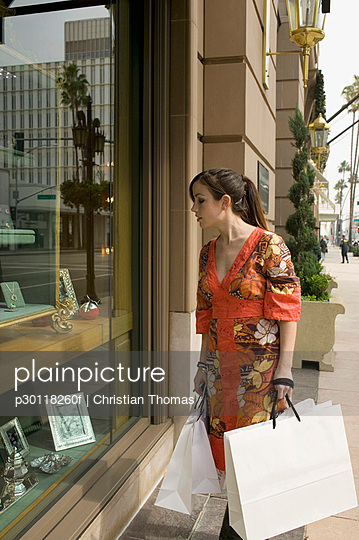 A woman looking through the window of a jewelry store, Rodeo Drive, Los Angeles, California