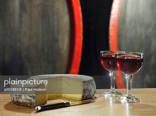 Two glasses of red wine and a wheel of cheese, still life