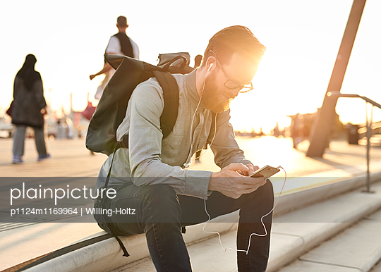 Mann sitzt auf Treppe mit Smartphone - p1124m1169964 von Willing-Holtz