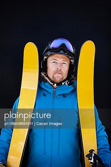 Man Holding Yellow Skis