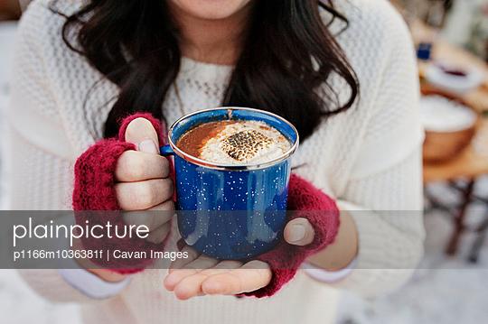 Woman holding mug with coffee
