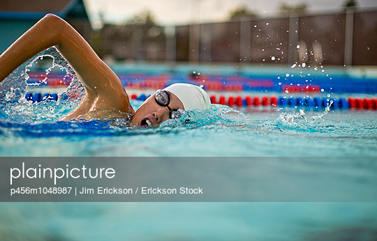 Young woman swimming the front crawl in a pool