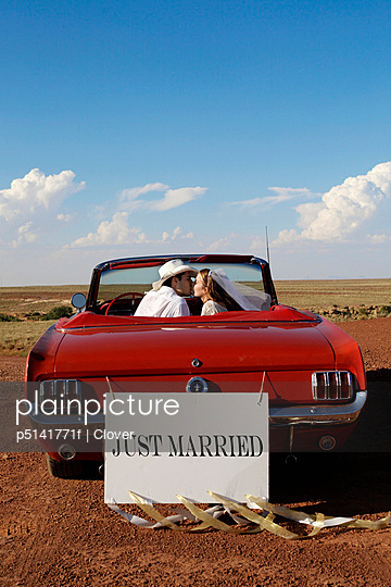 Newlyweds kissing in convertible