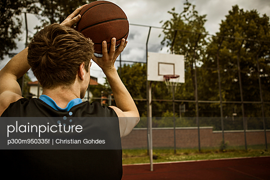 Young basketball player aiming for basketball hoop, back view