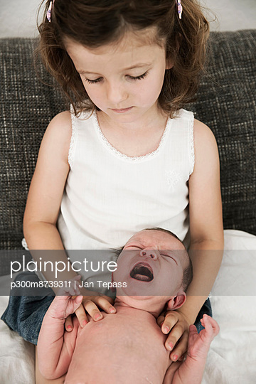 Little girl and her crying newborn brother at home
