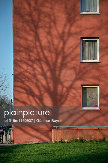 Schatten von blattlosem Baum auf roter Häuser Fassade, ehemalige Soldatensiedlung der Amerikaner, Neu-Ulm, Bayern, Deutschland - p1316m1160907 von Günther Bayerl