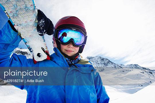 Boy holding skis on snowy mountain
