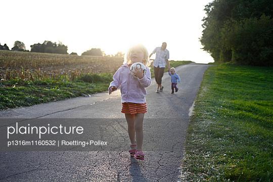 Kinder laufen auf einer kleinen Straße am Feldesrand im Abendlicht, MR, Bad Oeynhausen, Nordrhein-Westfalen, Deutschland - p1316m1160532 von Roetting+Pollex