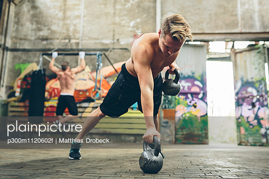 Young man having a workout with kettlebells