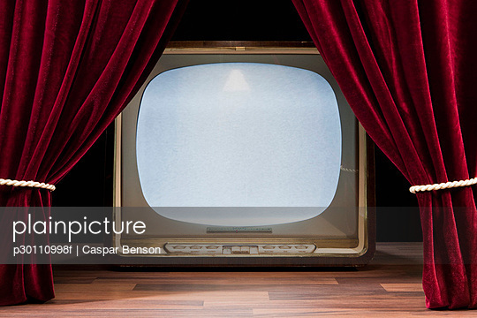 An Old Fashioned Television Behind Red Theatre Curtains