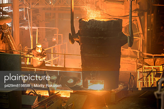 Elevated view of steel worker and molten bucket in steel foundry
