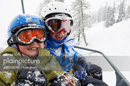 Snow-covered children in ski lift