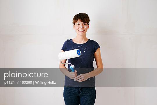 Junge Frau mit Farbrolle - p1124m1160260 von Willing-Holtz