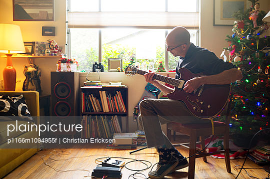 Man playing guitar while sitting on chair at home