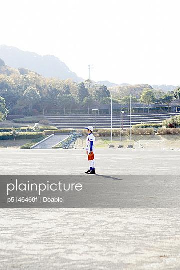 Boy in baseball uniform standing in field