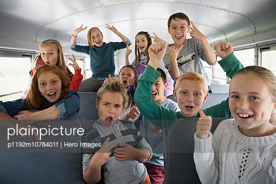 Portrait confident school kids gesturing on school bus