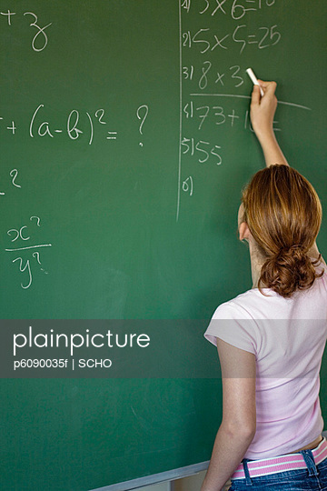 School girl (10-13) writing on blackboard in classroom