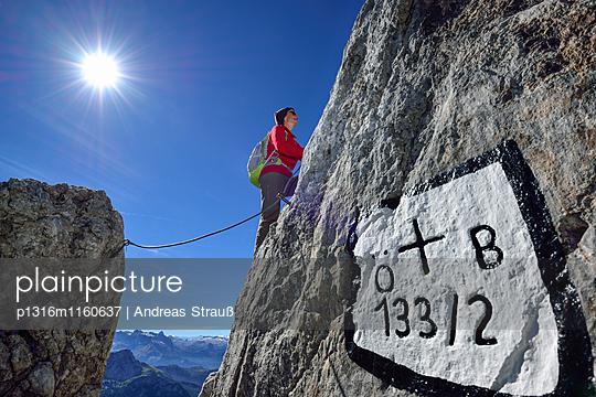 Frau steigt an Versicherungen zu Hohes Brett auf, Grenzmarkierung im Vordergrund, Hoher Göll, Nationalpark Berchtesgaden, Berchtesgadener Alpen, Oberbayern, Bayern, Deutschland - p1316m1160637 von Andreas Strauß