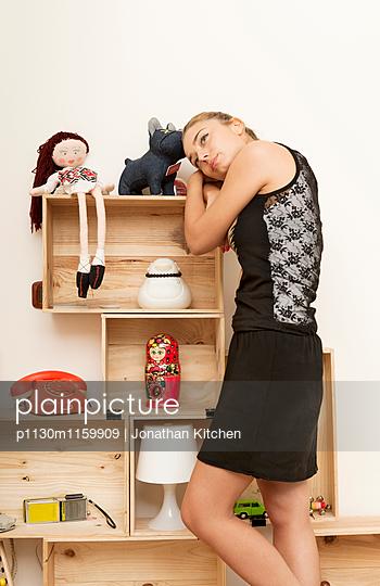Frau lehnt an einem Regal - p1130m1159909 von Jonathan Kitchen