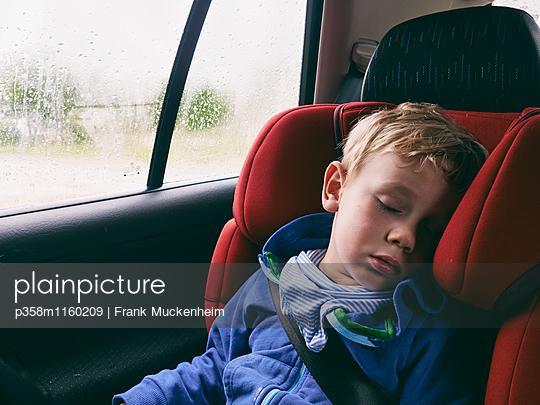 Kleiner Junge schläft im Kindersitz - p358m1160209 von Frank Muckenheim