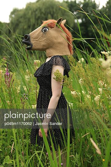 Frau mit Pferdemaske im Blumenfeld - p045m1170062 von Jasmin Sander