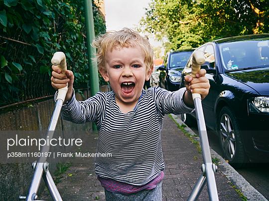 Kleiner Junge schiebt eine Kinderkarre - p358m1160197 von Frank Muckenheim