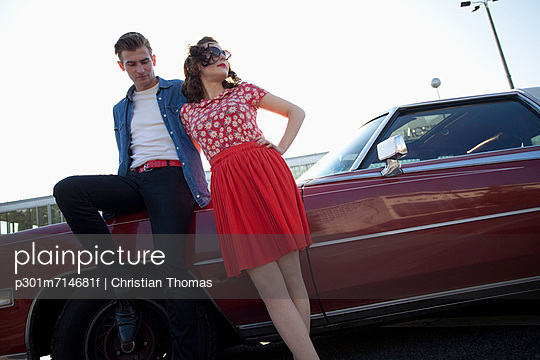 A cool, rockabilly couple leaning against a vintage car