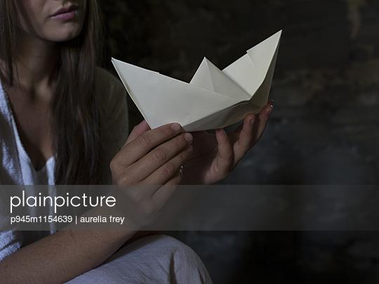Junge Frau mit Papierschiffchen - p945m1154639 von aurelia frey