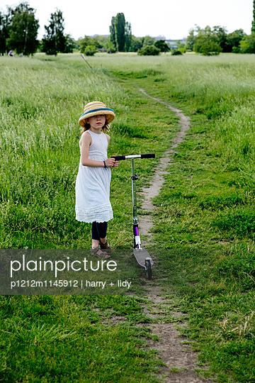Mädchen mit einem Roller auf einem Feldweg - p1212m1145912 von harry + lidy