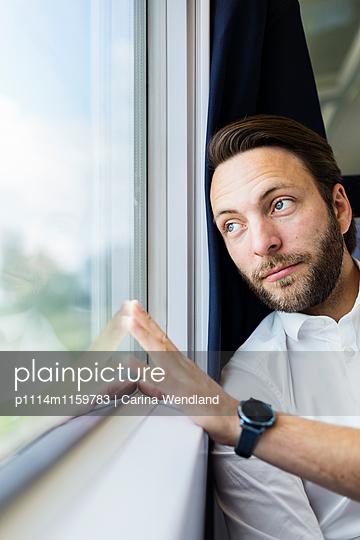 Mann schaut aus dem Zugfenster - p1114m1159783 von Carina Wendland