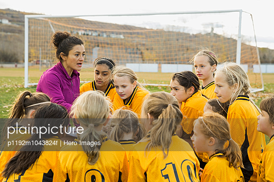 Soccer coach discussing strategy with players on field