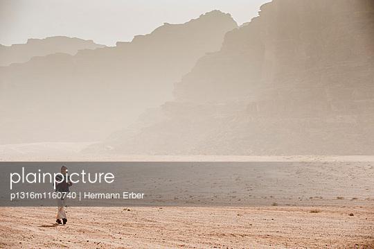 Frau wandert im diesigen Wadi Rum, Jordanien, Naher Osten - p1316m1160740 von Hermann Erber
