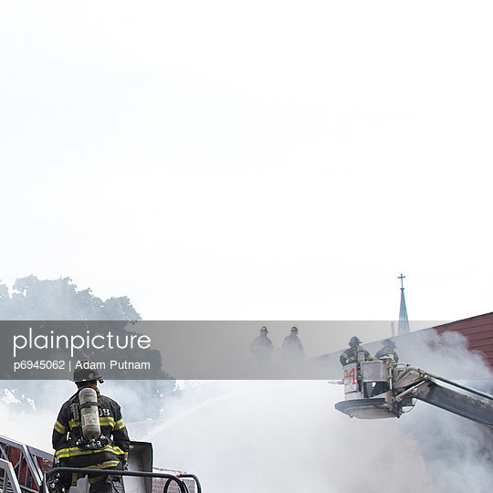 Firemen Fighting a Fire Through Smoke With Church in Background, Brooklyn, New York, USA