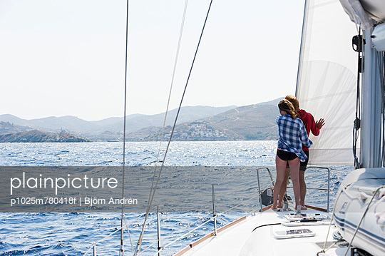 Rear view of a couple in the bow of a sailboat overlooking the Aegean sea